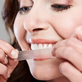 Woman placing a whitening strip