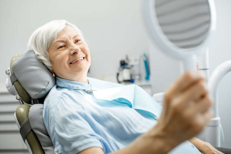 Mature female patient smiling into a mirror